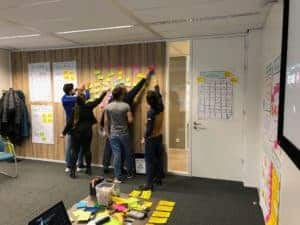 Students working together while putting post-it's on the wall